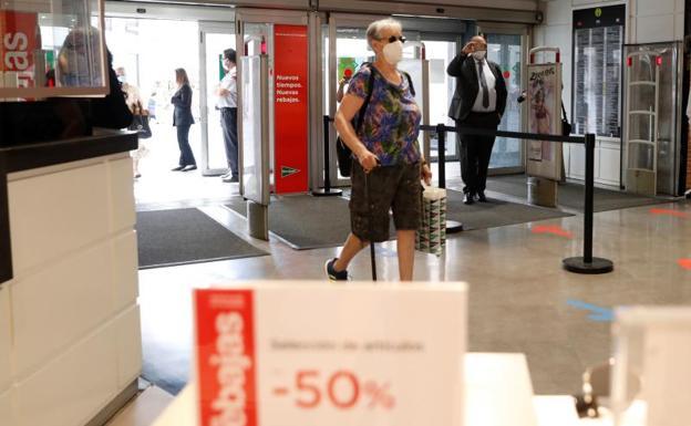 Una mujer accede a un centro comercial de la madrileña calle Preciadas  EFE