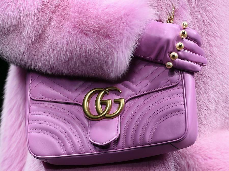 Una modelo desfila para Gucci con una abrigo de pelo y un bolso de piel  rosas 1c62d5296eb