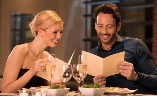 Una pareja ojea la carta de un restaurante. /