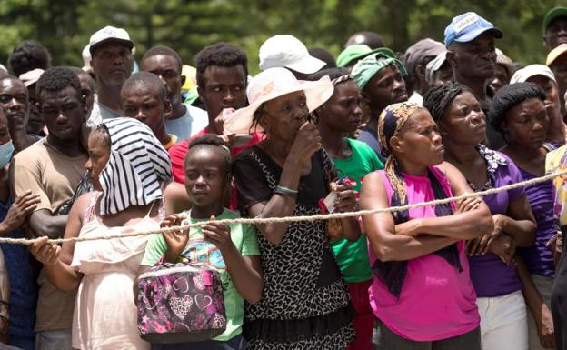 People line up to receive food, in Haiti